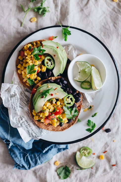 Crispy tostadas with spicy black beans, sweet corn salsa and avocado slices #summer #vegan | TheAwesomeGreen.com