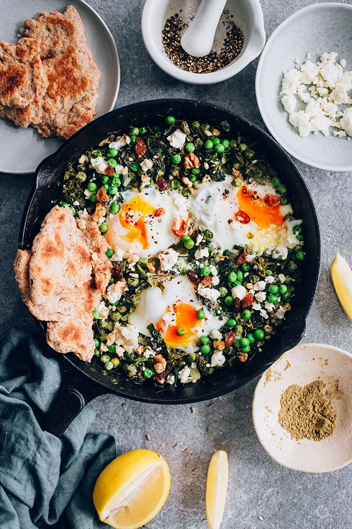 Green Shakshuka with spinach, green peas and spices, topped with creamy goat cheese and walnuts