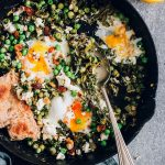 Green shakshuka served in a skillet, made with spinach and peas and topped with goat cheese and crushed walnuts